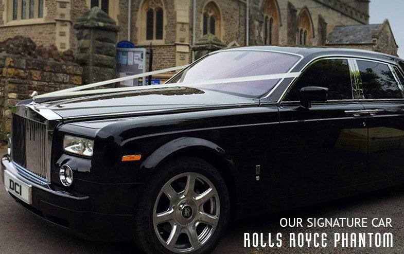 Rolls Royce Phantom dressed in white ribbons waiting outside of church